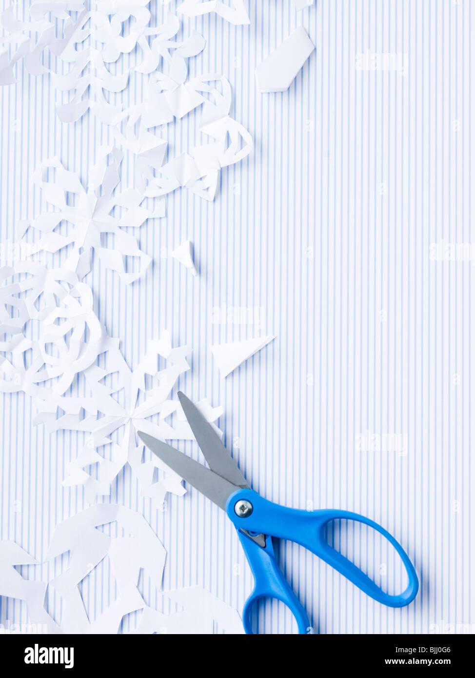 Forbici e fiocchi di neve di carta Immagini Stock
