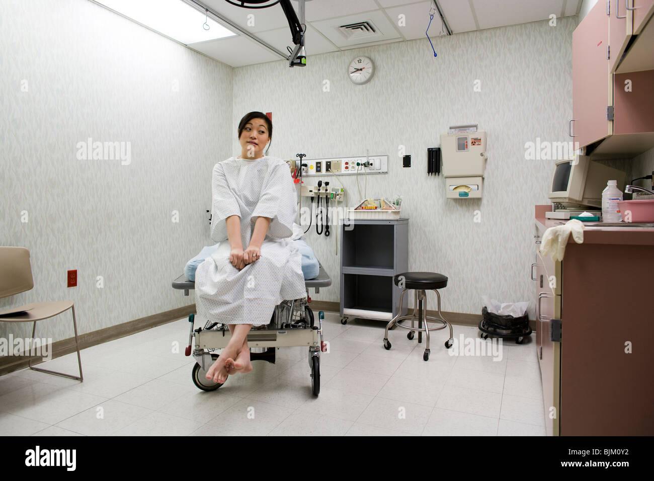 Paziente femmina di trepidante attesa nella sala esame Immagini Stock