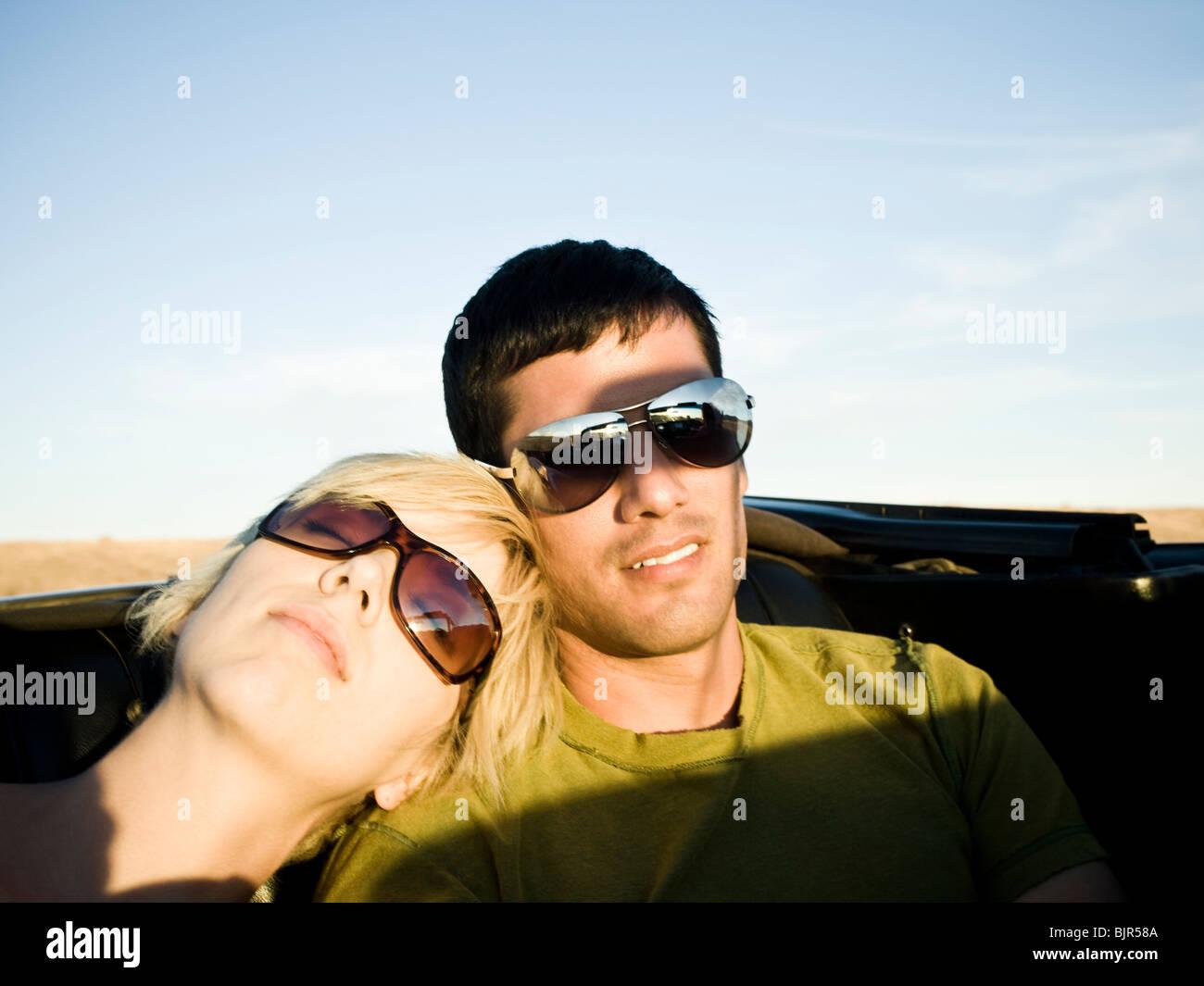 L uomo e la donna accanto a un rosso convertibili Immagini Stock