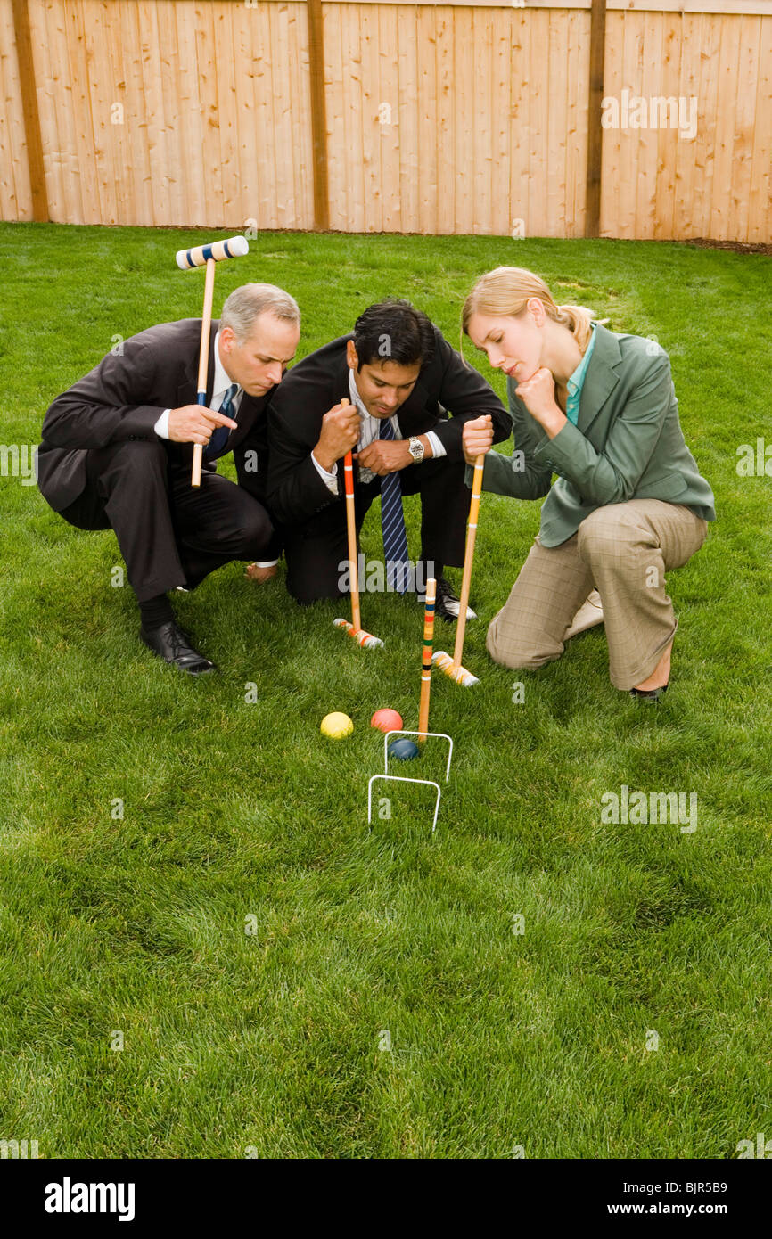Tre uomini d'affari giocando croquet Immagini Stock