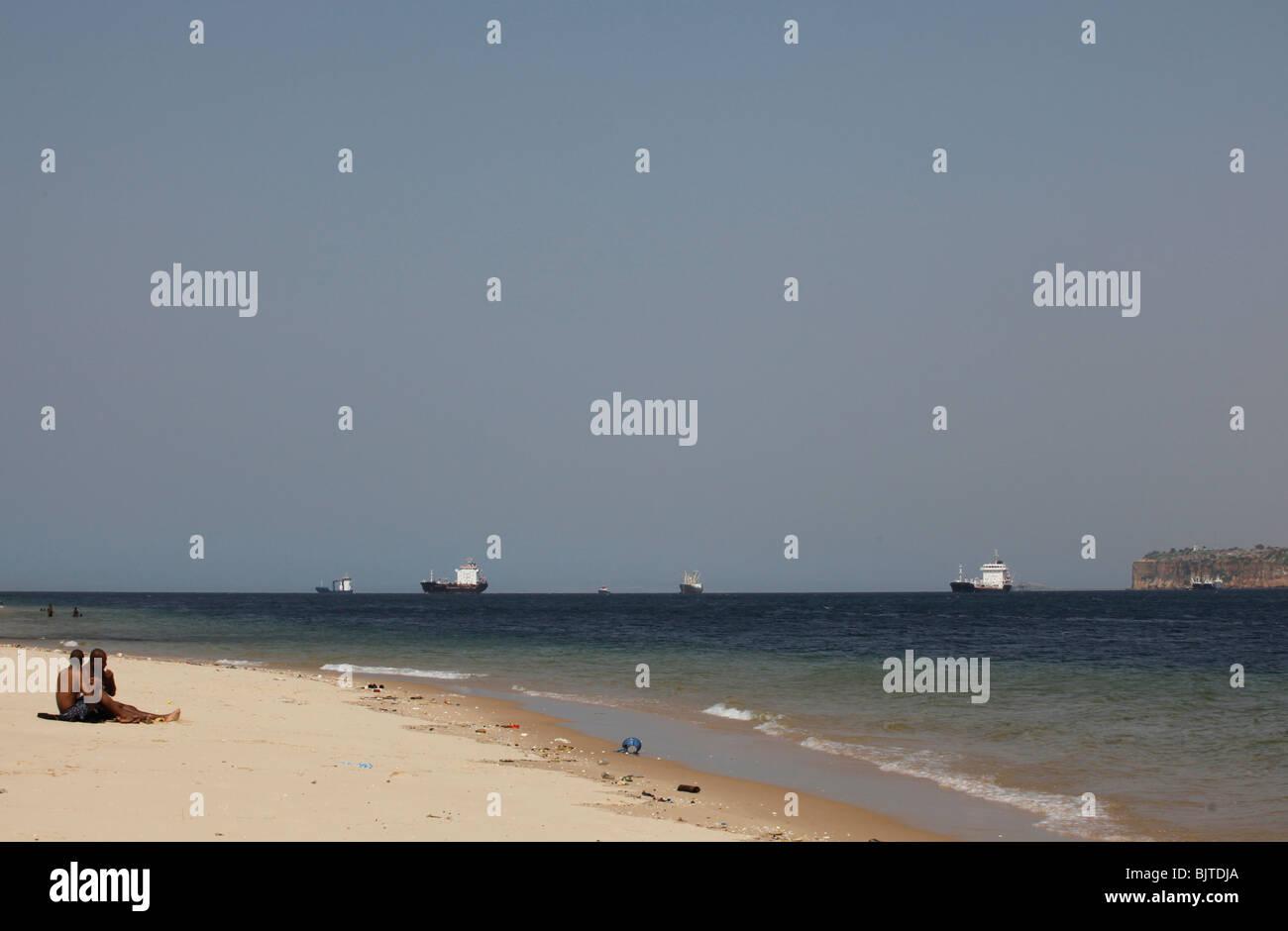 Navi e navi cisterna in attesa di attraccare in porto. Come si vede dalla spiaggia alla fine di Ilha. Luanda. Angola. Immagini Stock