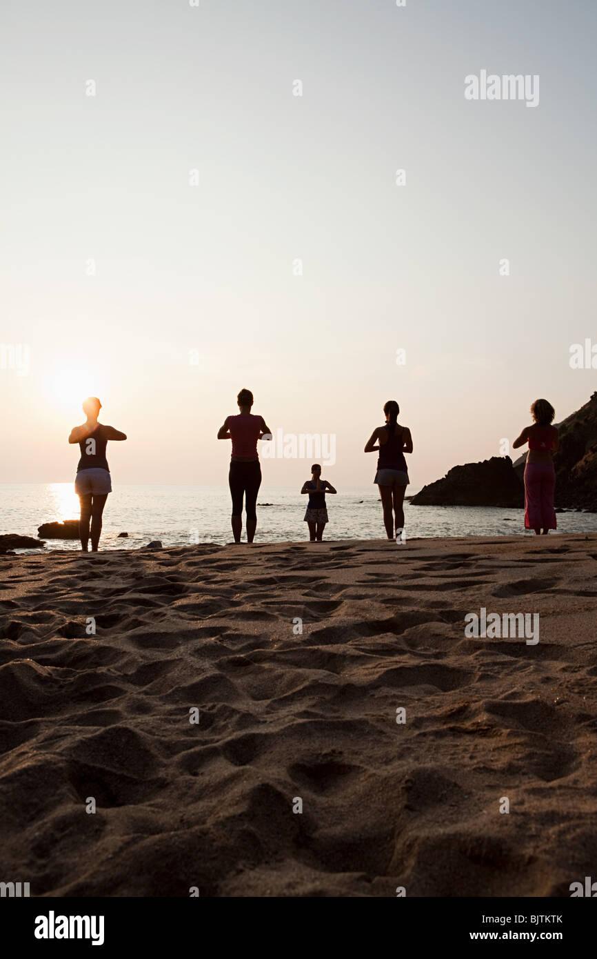 Le donne a praticare yoga sulla spiaggia al tramonto Immagini Stock