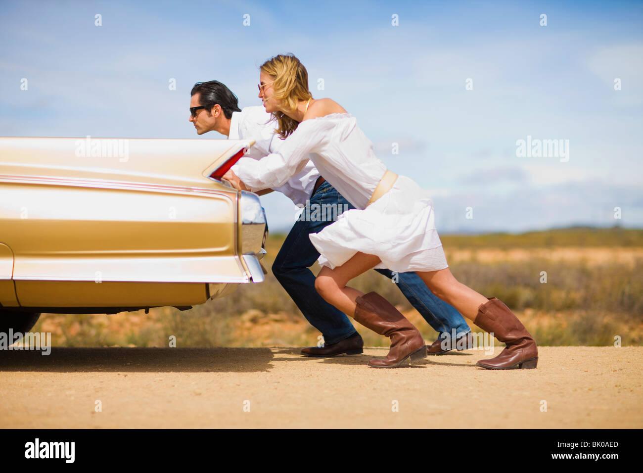 Giovane spingendo un auto Immagini Stock