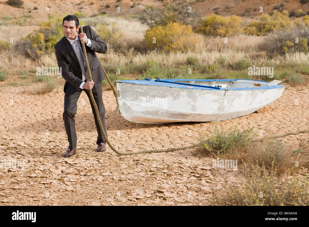 Imprenditore il traino di una barca nel deserto Immagini Stock