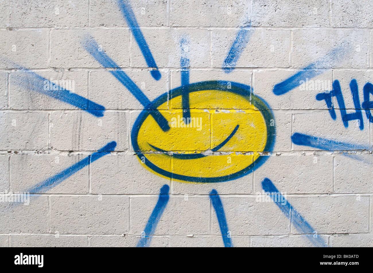 Sun Graffiti spruzzato su bianco muro di mattoni Immagini Stock