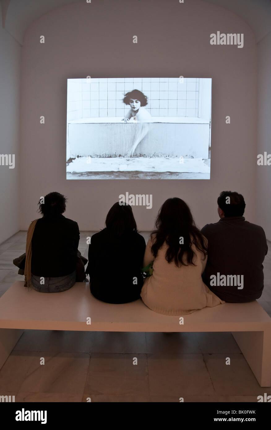 Ai visitatori la visione di un Buster Keaton filmato nel Centro de Arte Reina Sofia, Madrid, Spagna Immagini Stock