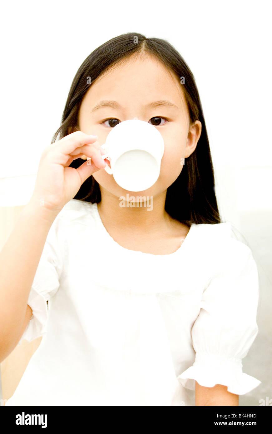Giovane ragazza asiatica sorseggiate una tazza di tè Immagini Stock
