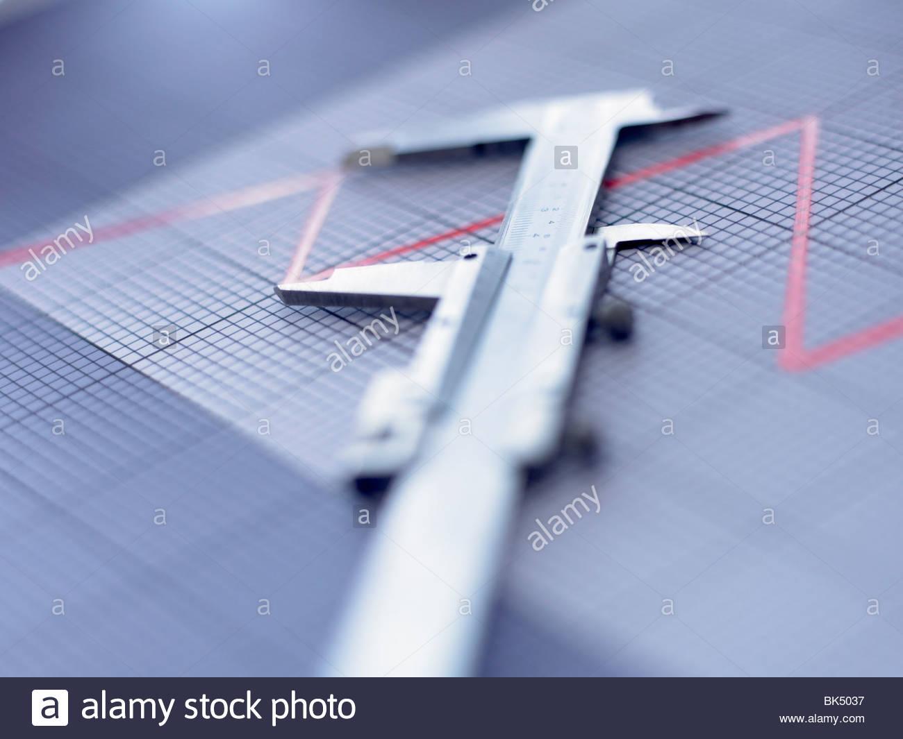 Chiusura del calibro a corsoio su grafico Immagini Stock