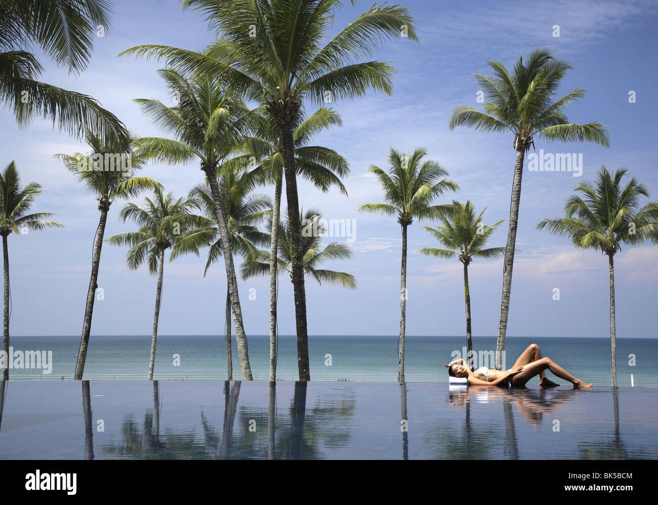 Giovane donna a rilassarci in piscina con palme e il mare oltre Immagini Stock