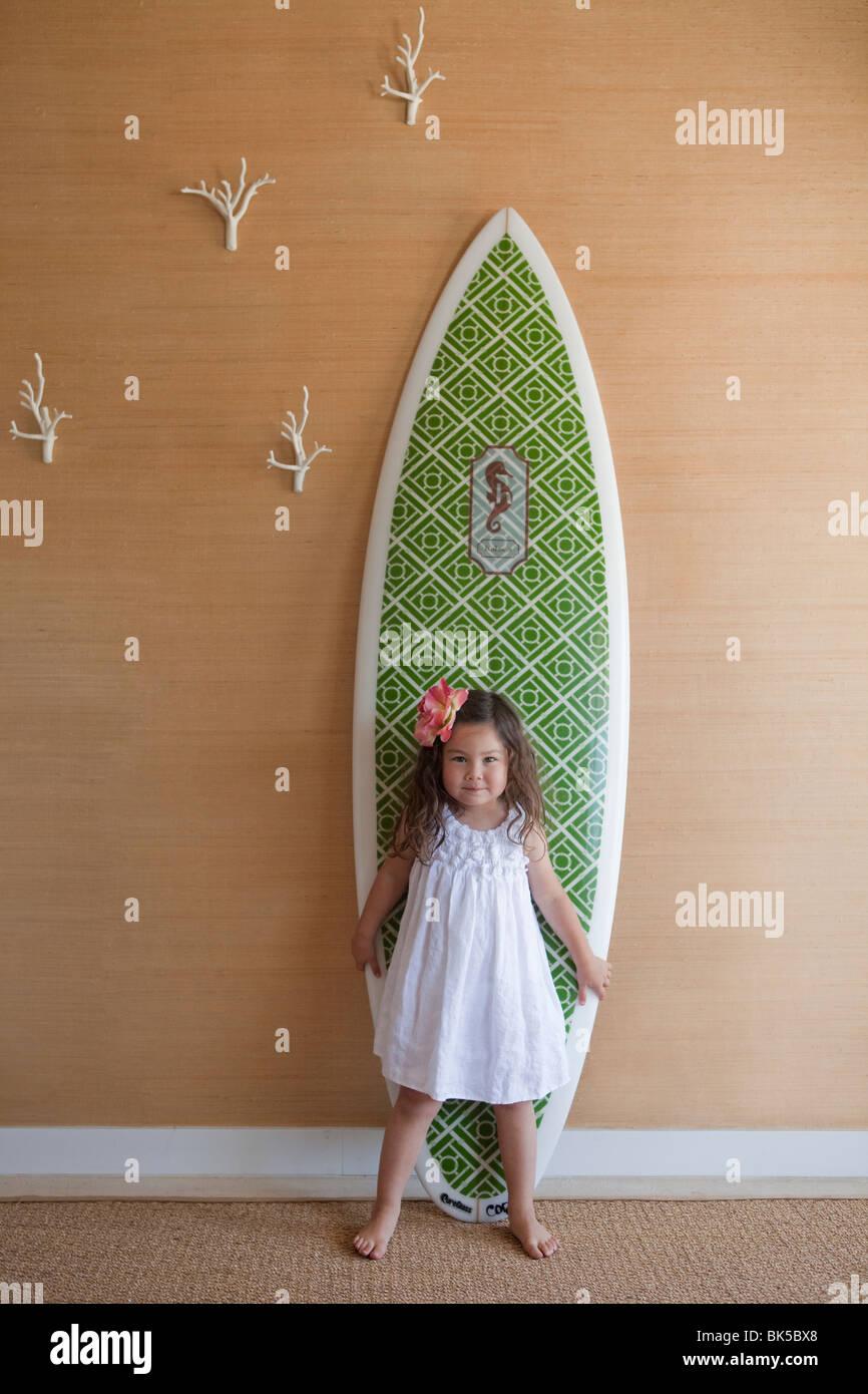 Ragazza in abito bianco in posa nella parte anteriore della tavola da surf Foto Stock