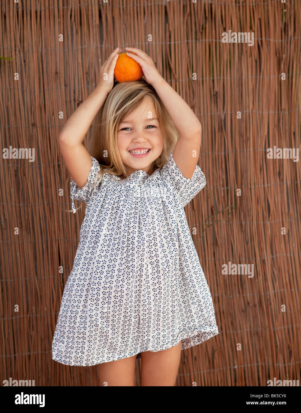 Giovane ragazza in abito di Sun in possesso di un arancione sul suo capo Immagini Stock