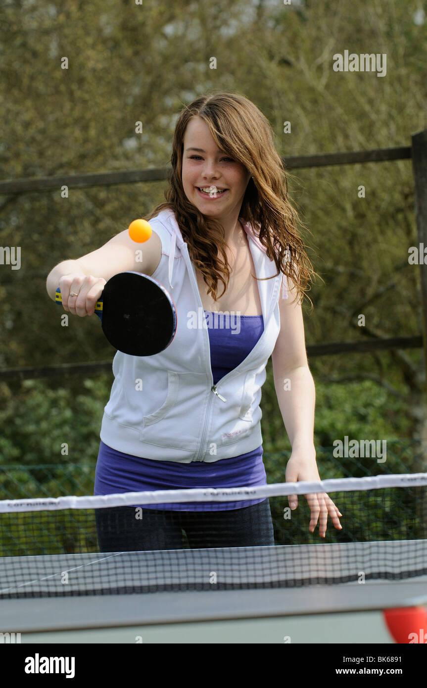 Ragazza adolescente giocando una partita di tennis da tavolo nel suo giardino Immagini Stock