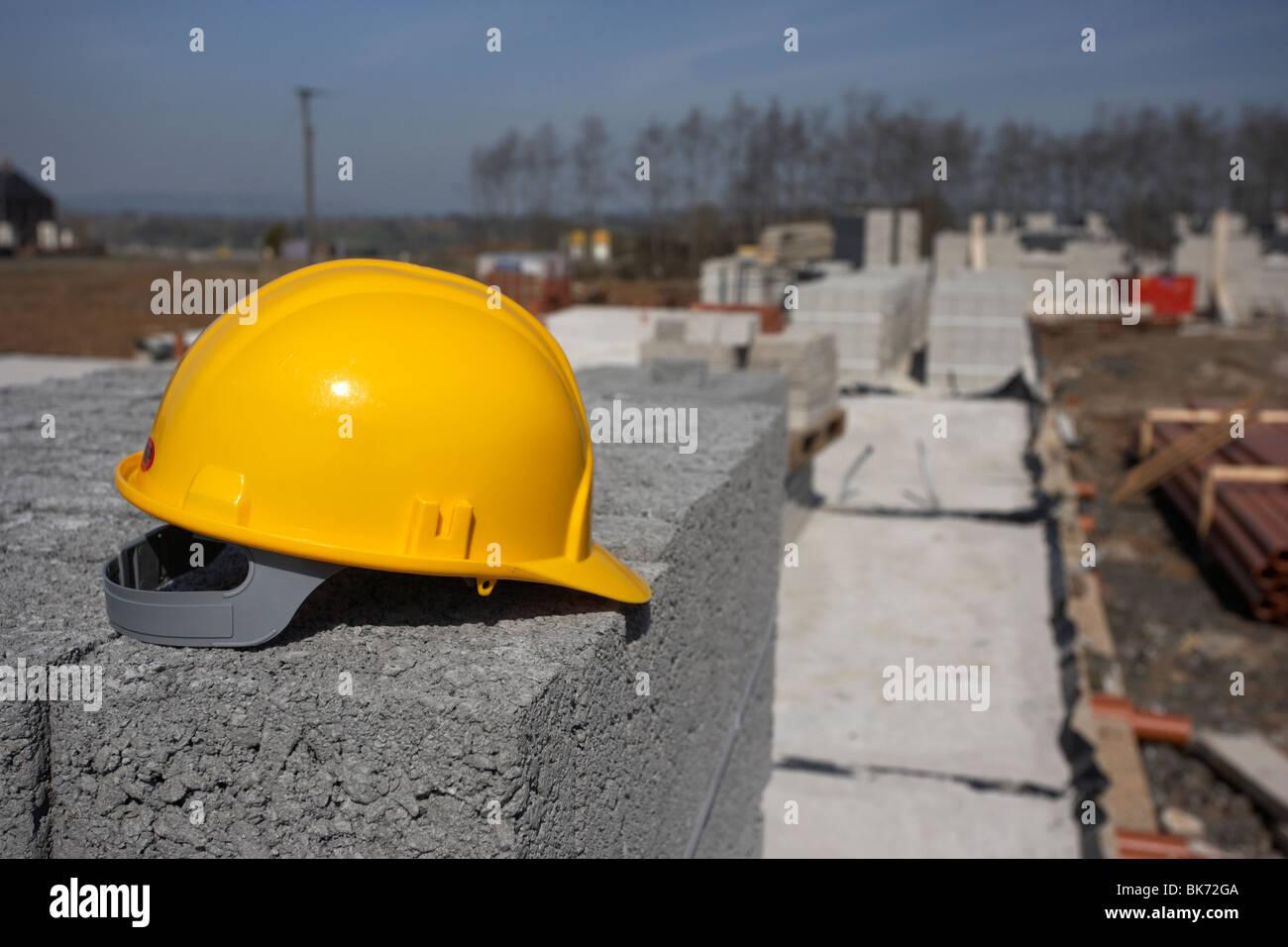 Elmetto seduto su una pila di brezza edificio in calcestruzzo blocchi sul fermo costruzione dell'edificio sito Immagini Stock