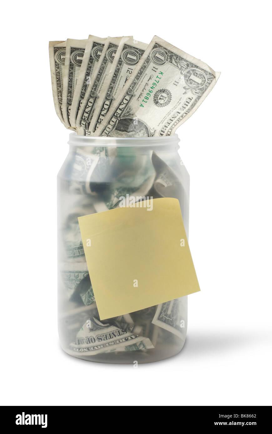 Vaso di cassa traboccante con noi le fatture del dollaro e un bigliettino giallo. Immagini Stock
