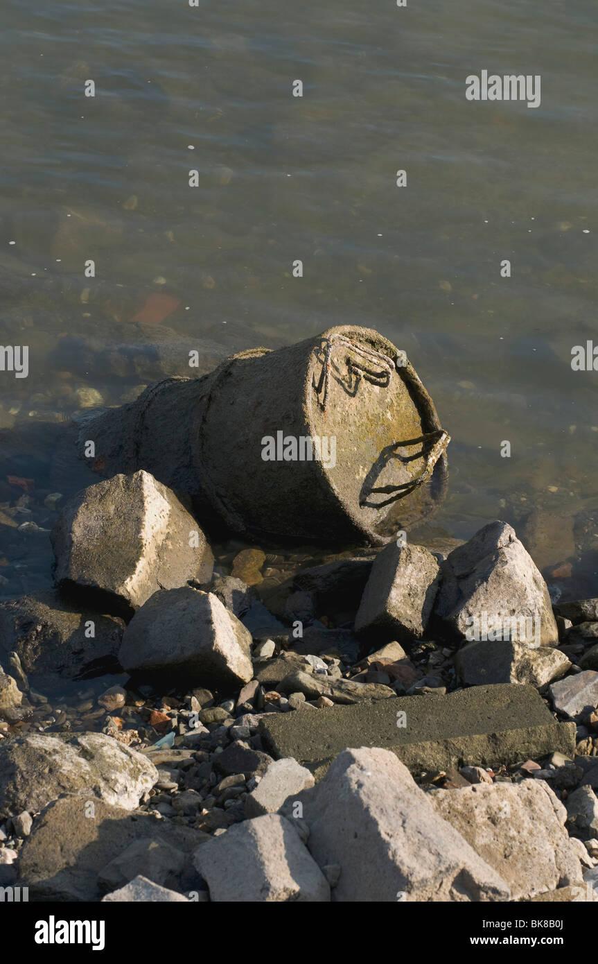 Inquinamento, vecchio tamburo di metallo lavato fino sulla banca del fiume Reno Immagini Stock