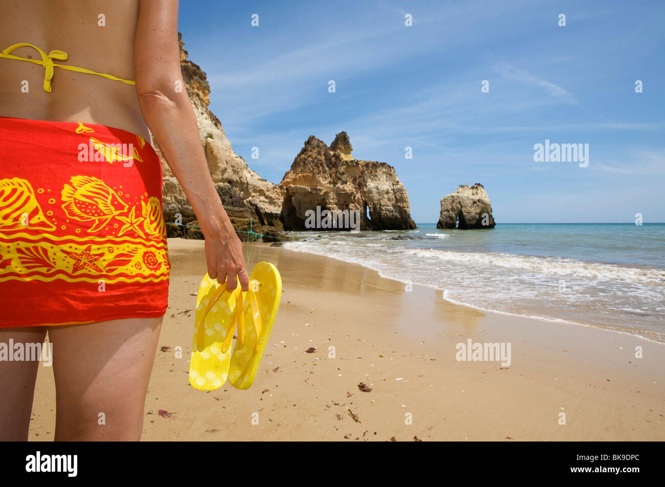 Donna sulla spiaggia con flip-flop, Praia dos Tres Irmaos vicino a Alvor, Algarve, Portogallo, Europa Immagini Stock