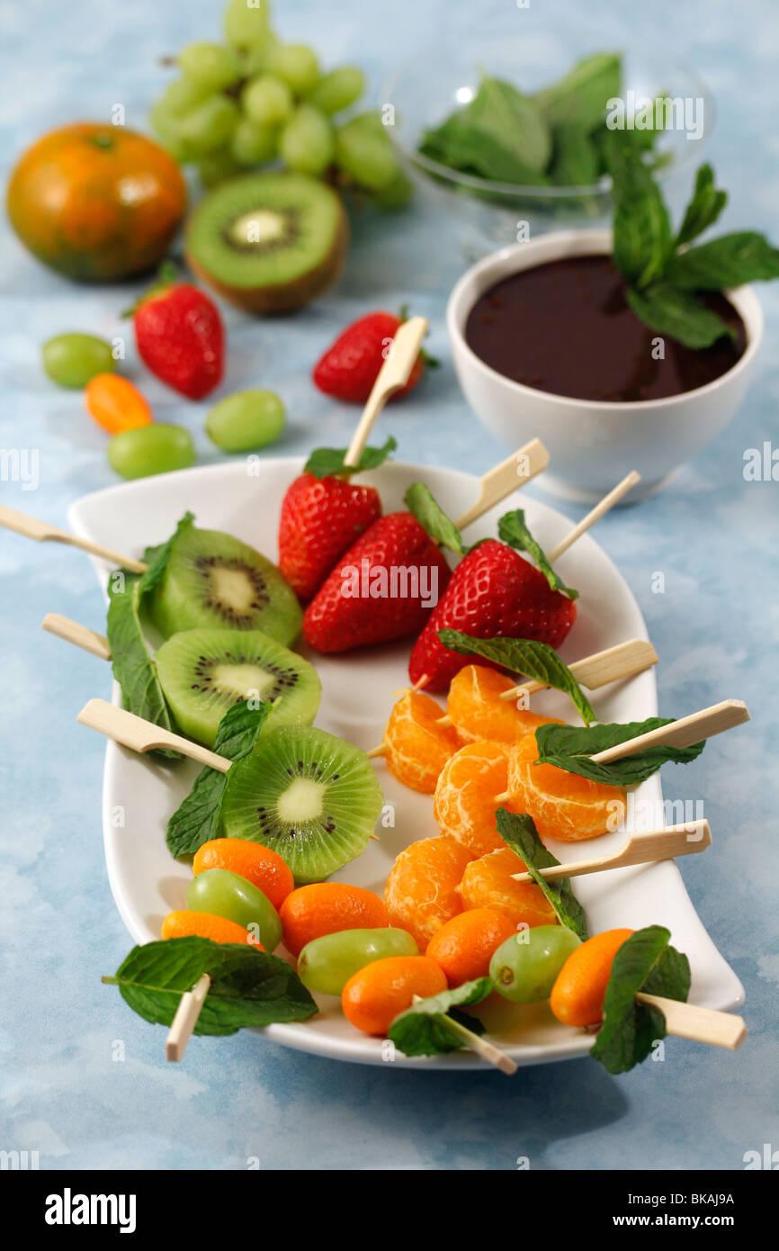 Gli spiedini di frutta con cioccolato e menta. Ricetta disponibile. Immagini Stock