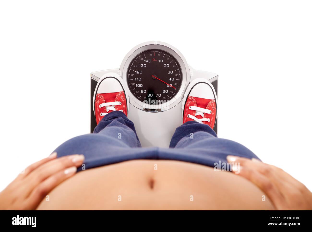 Atletica Giovane ragazza misurando il suo peso su una bilancia Immagini Stock