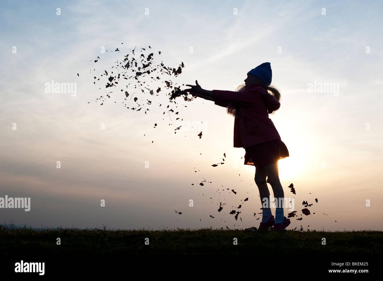 Giovane ragazza divertirsi gettando le foglie. Silhouette Immagini Stock