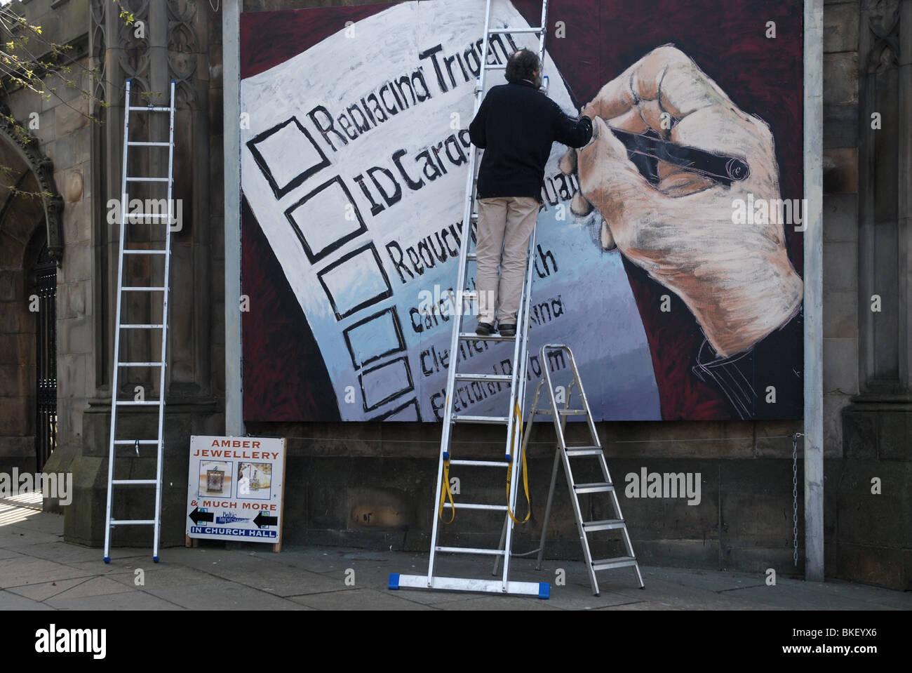 Un murale essendo dipinta su un muro della chiesa commentando i temi delle prossime elezioni nel Regno Unito. Immagini Stock