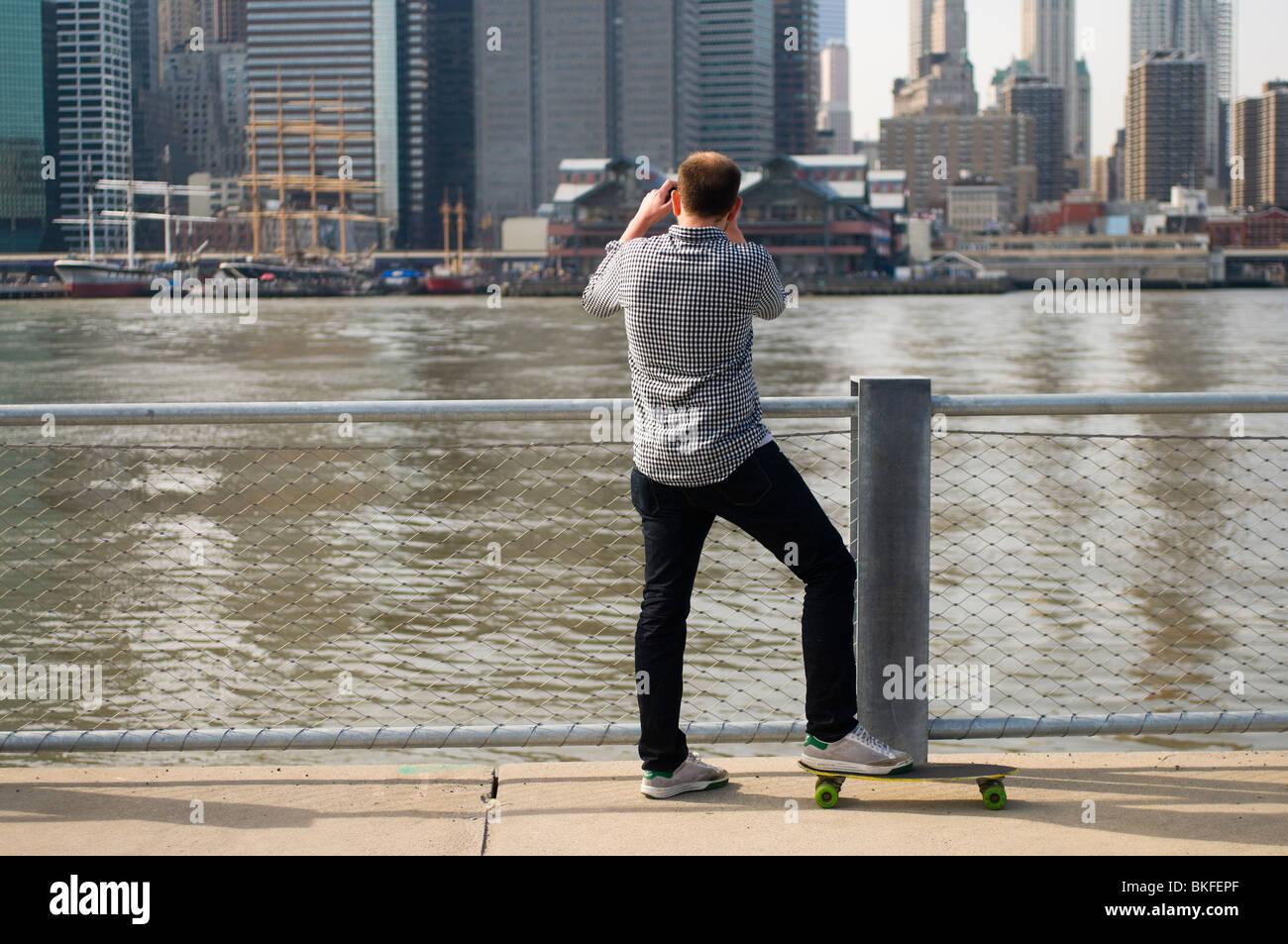 Brooklyn NY - Aprile 2010 - Uomo su uno skateboard prende uno snapshot del South Street Seaport, dal recentemente Immagini Stock