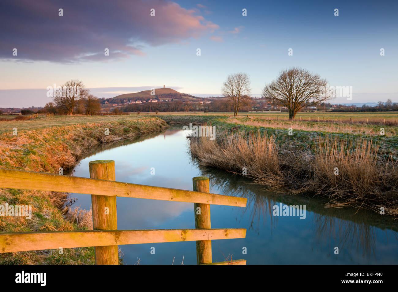 La prima luce del mattino a Glastonbury Tor visto dal fiume Brue sui livelli di Somerset, Glastonbury, Somerset, Foto Stock