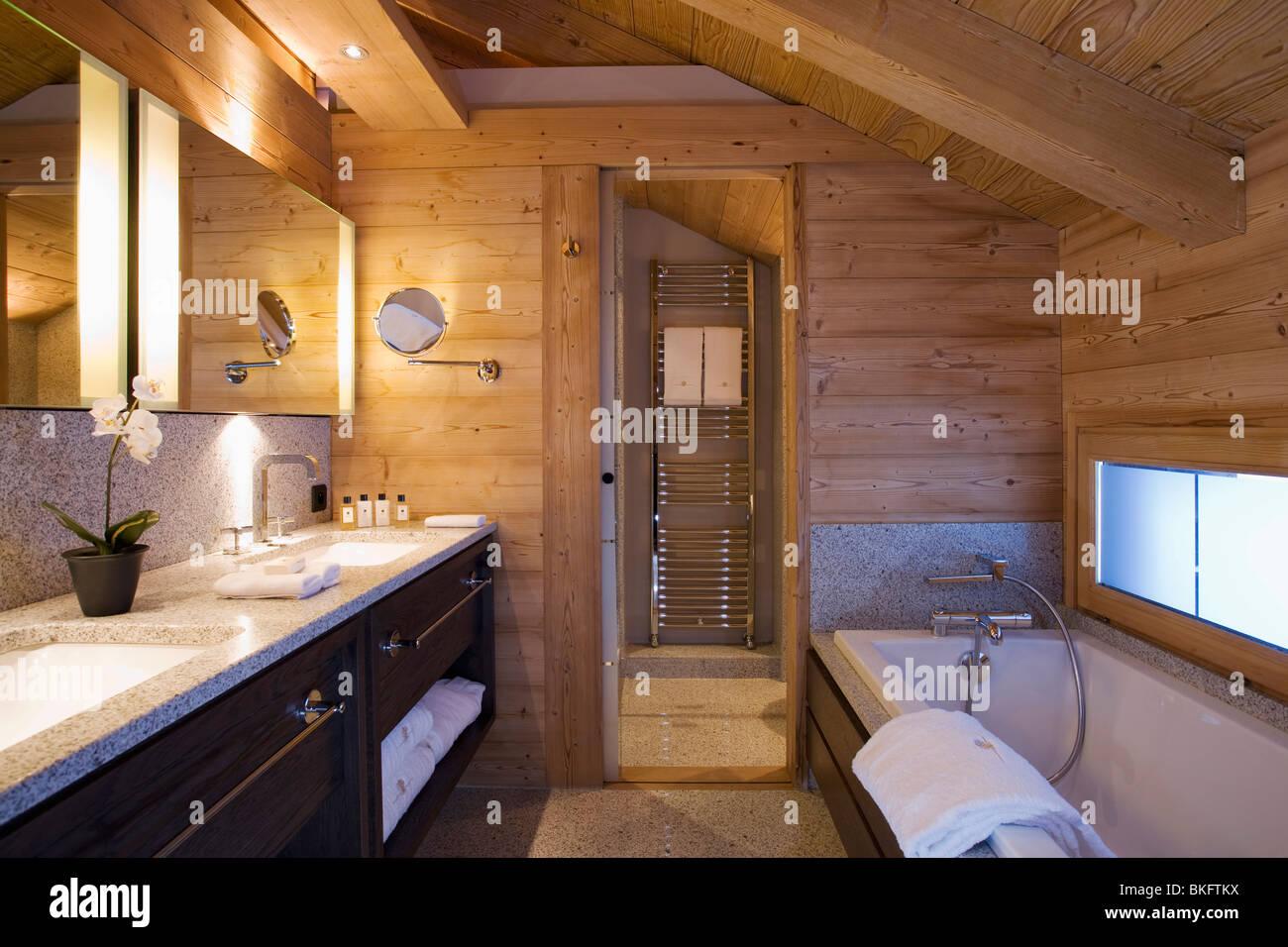 Le pareti in legno e il soffitto inclinato di bagno moderno in chalet di montagna con - Illuminazione casa montagna ...