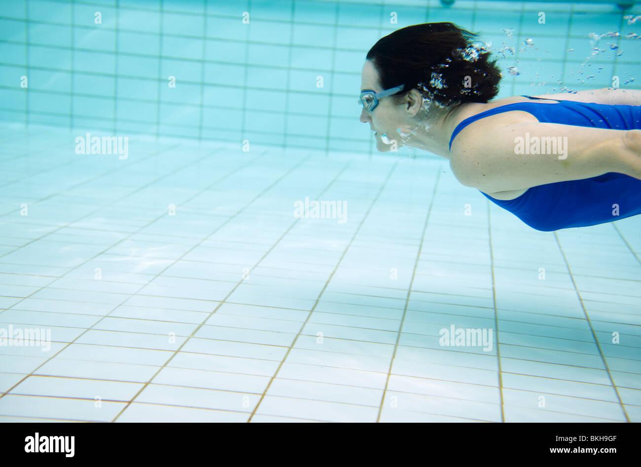 0be00c9576 Donna blu in costume da bagno nuotare sotto l'acqua in piscina Foto ...
