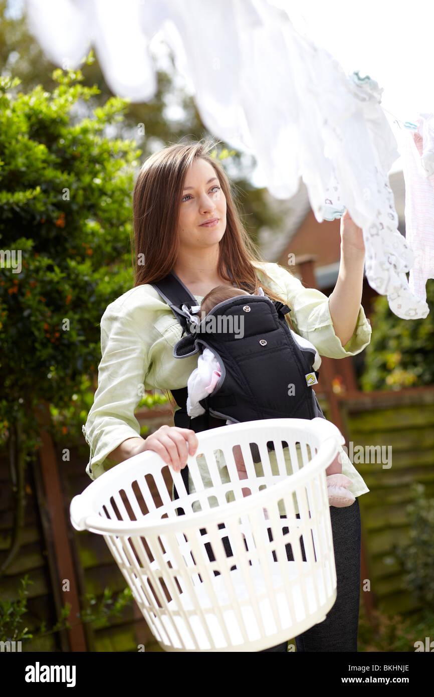 Donna con bambino tenuto nel lavaggio dalla linea Immagini Stock
