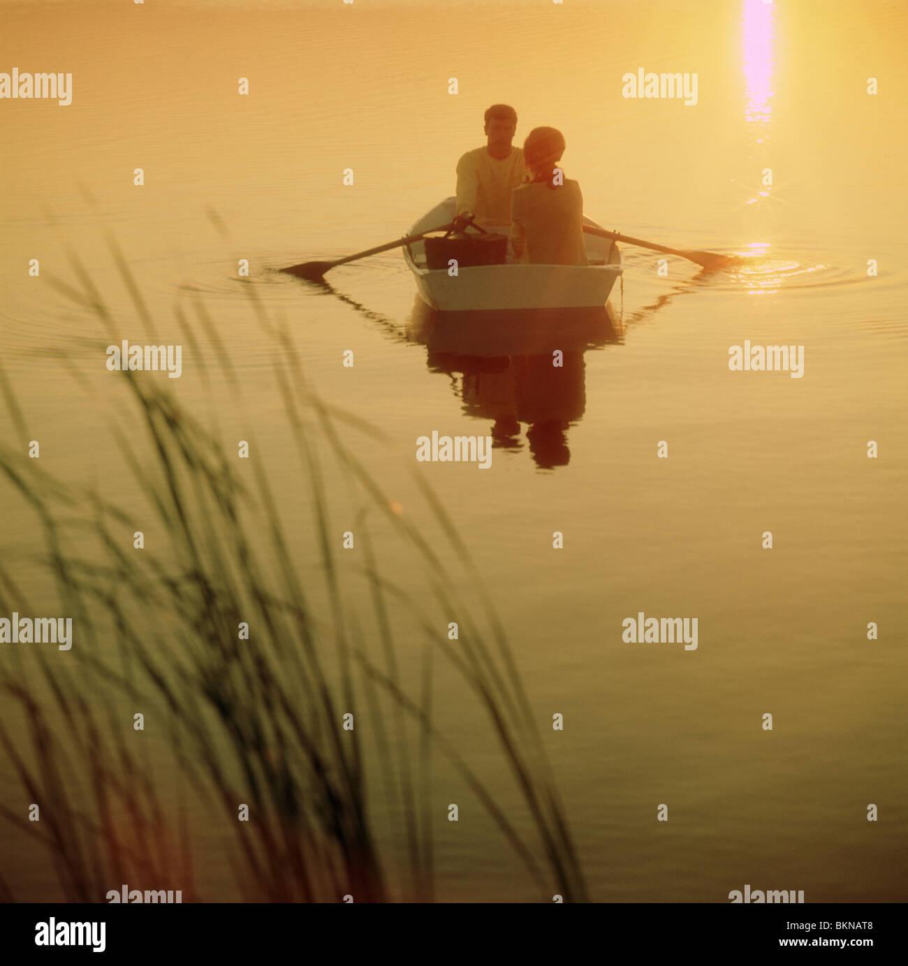 Giovane su una barca a remi durante il tramonto Immagini Stock