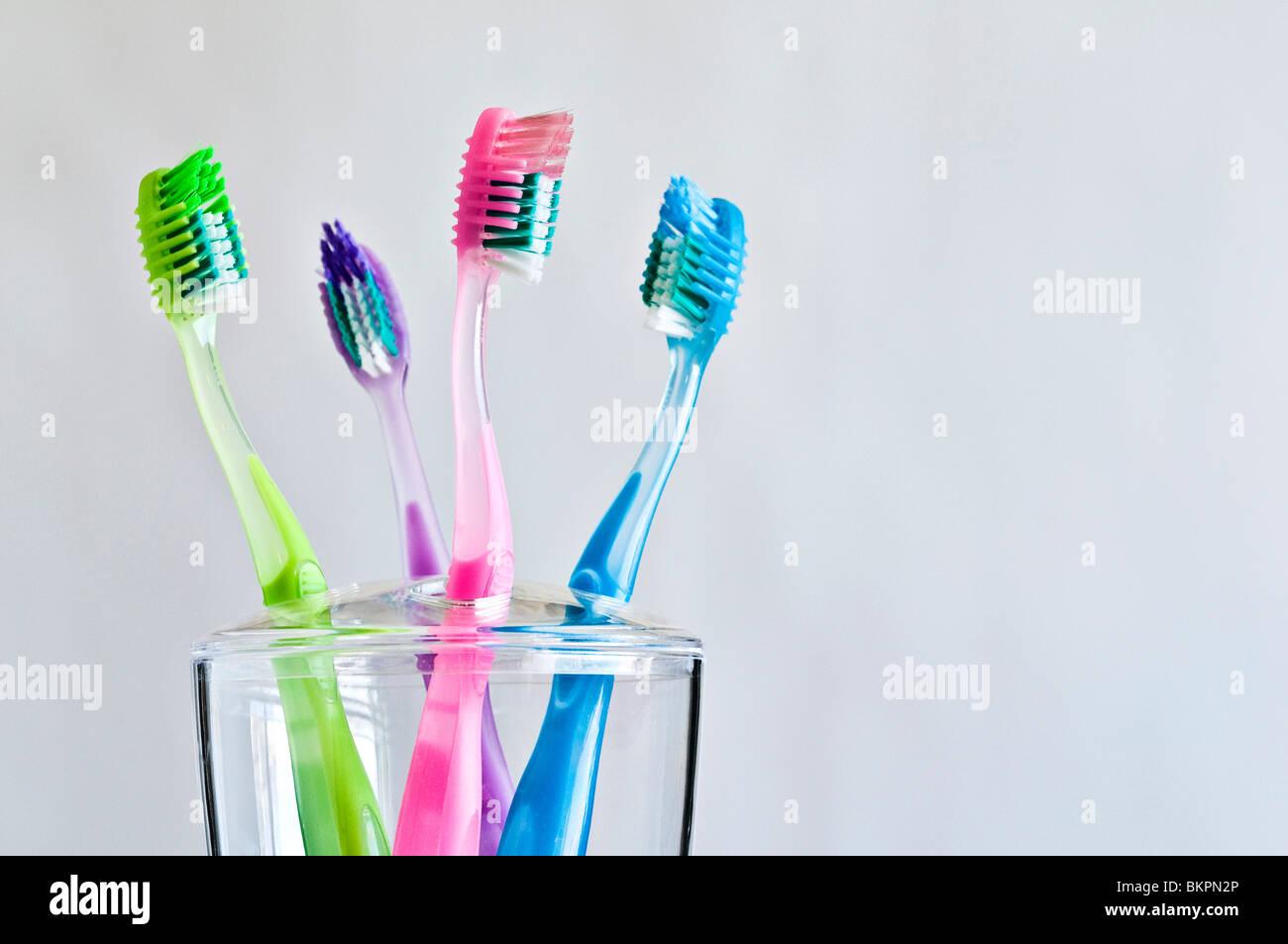 Quattro diversi spazzolini da denti colorati in famiglia titolare dello spazzolino da denti. Immagini Stock