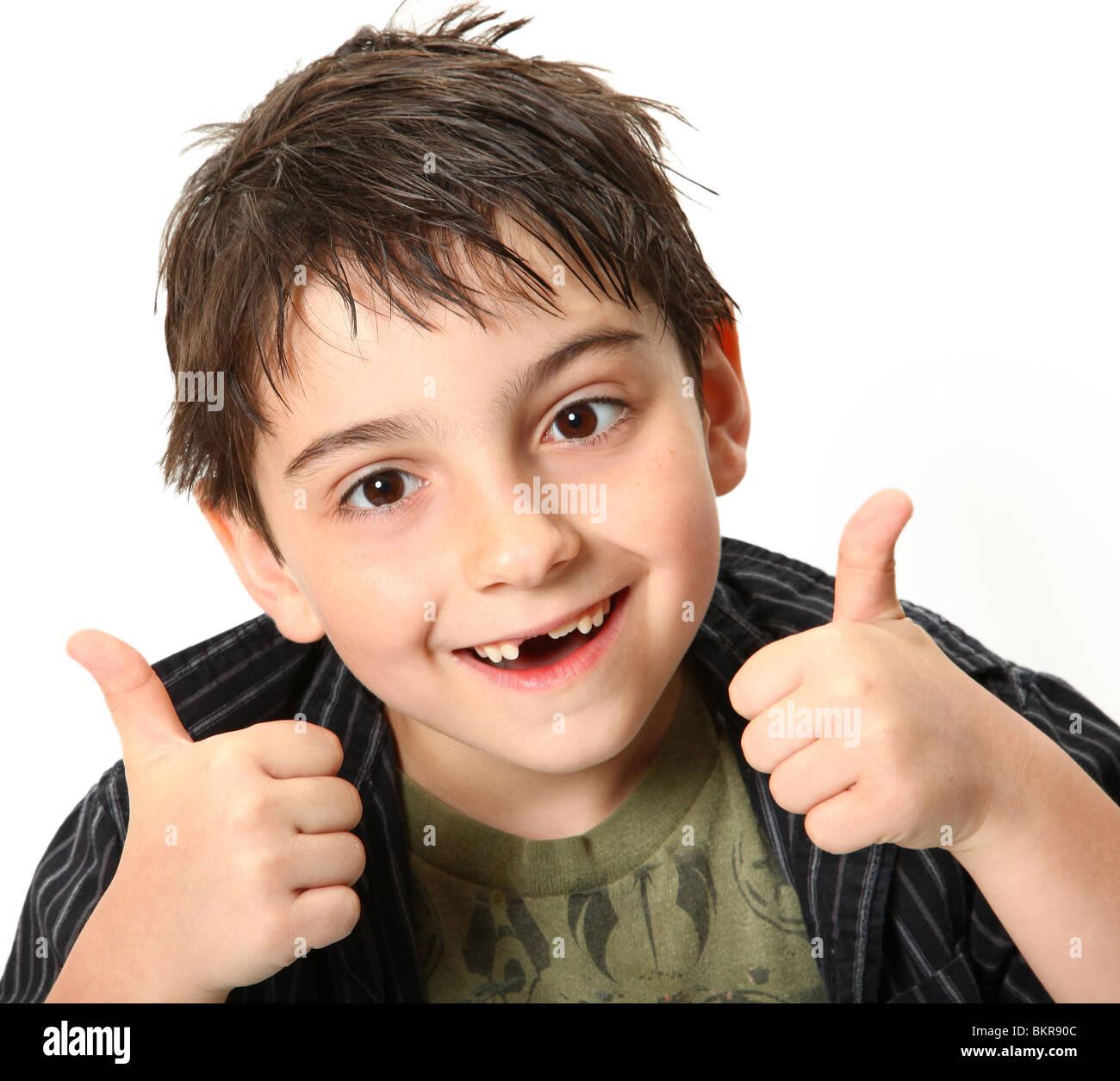 Silly sette anno vecchio ragazzo rendendo gli occhi incrociati e pollice su gesto. Immagini Stock