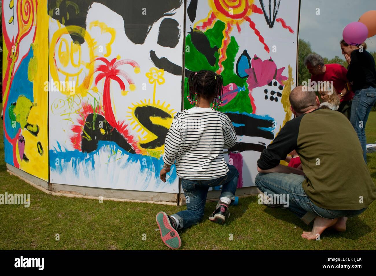 """Famiglie alla celebrazione del mondo """"commercio equo"""" giorno, con bambini pittura parete, sul prato di Immagini Stock"""