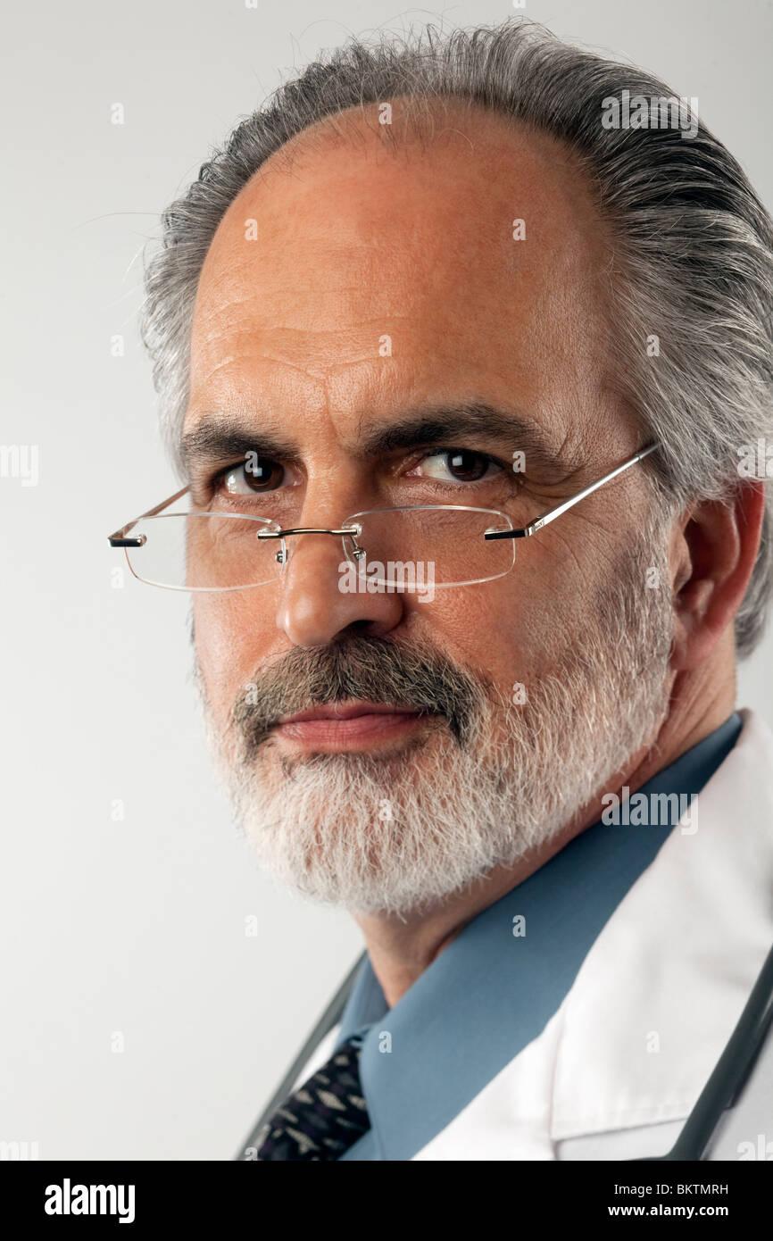 Close-up verticale di un dottore che indossa occhiali e un bianco camice. Egli guarda la fotocamera con un espressione Immagini Stock
