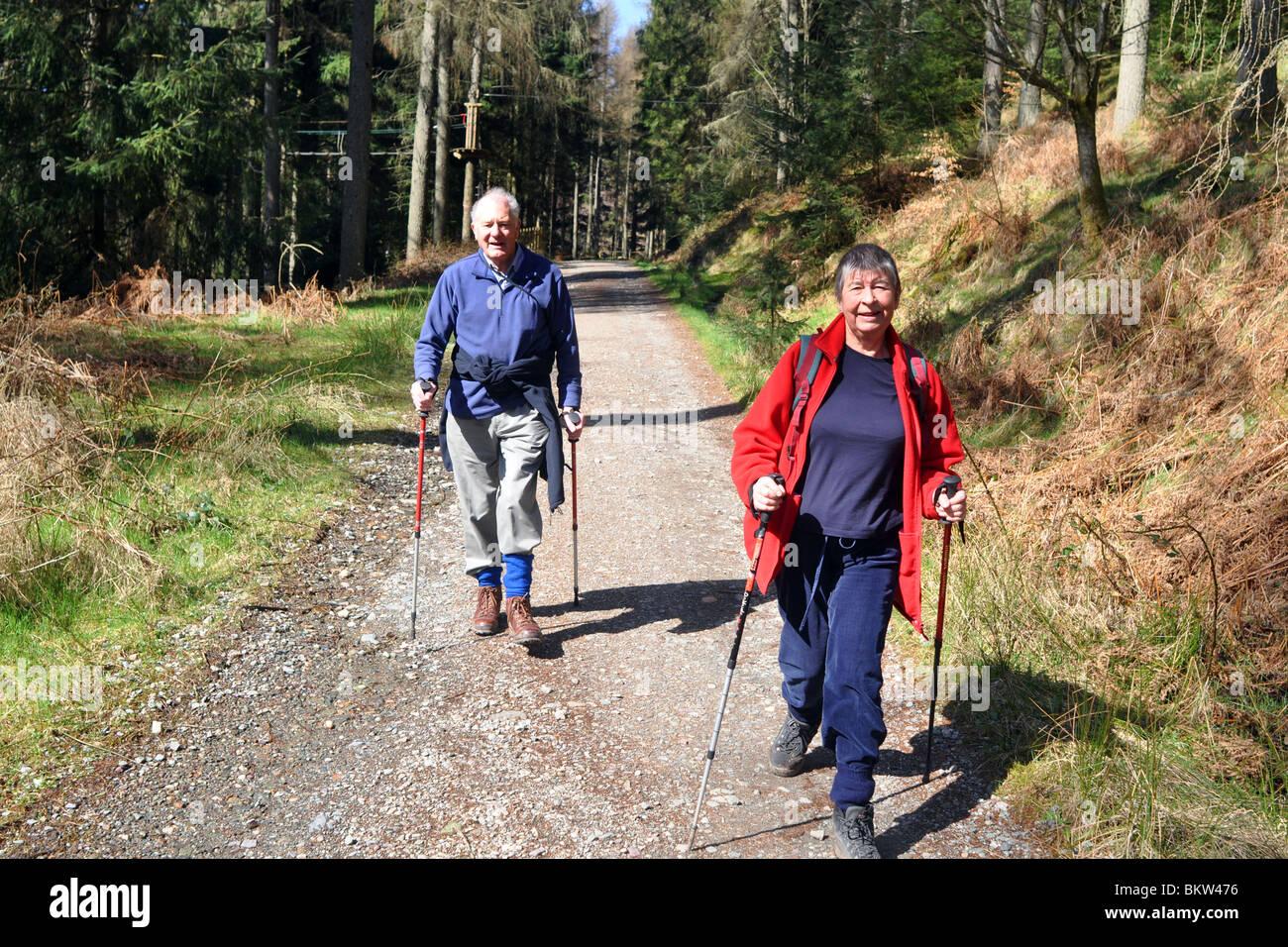 Persone anziane attive andare passeggiate in collina nel Trossachs National Park, Scozia Foto Stock