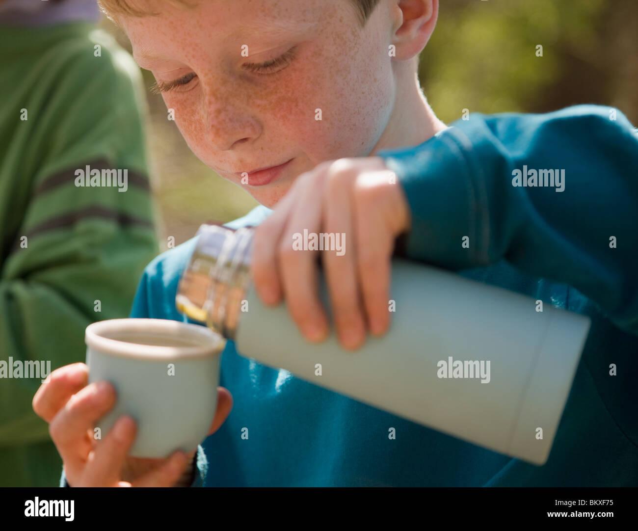 Chiusura del giovane ragazzo versando acqua dalla beuta isolata Foto Stock