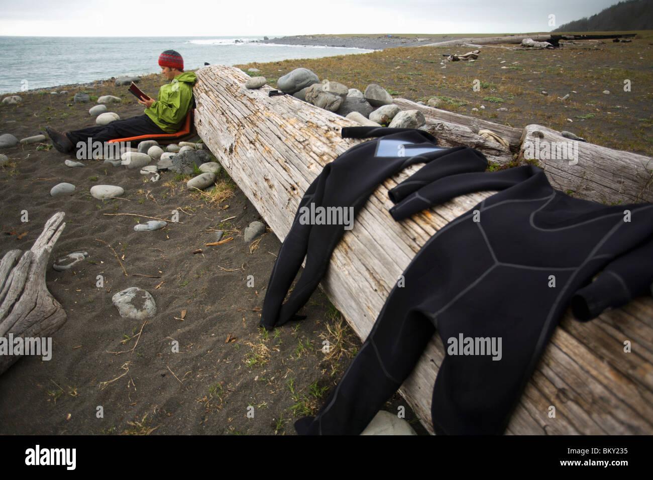 Un uomo legge un libro a camp sulla costa perso, California. Immagini Stock