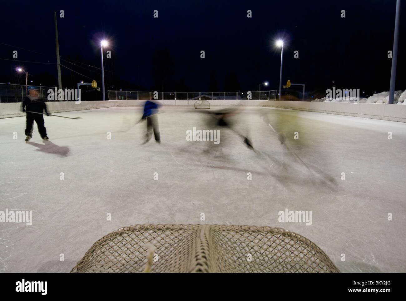 Una famiglia gioca un gioco di pick-up hockey presso la locale scuola elementare la pista di pattinaggio su ghiaccio Immagini Stock