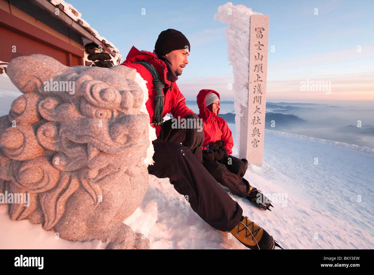 Due persone sono in appoggio sul bordo del vertice del Monte Fuji, Honshu, Giappone accanto a un tradizionale scultura Immagini Stock