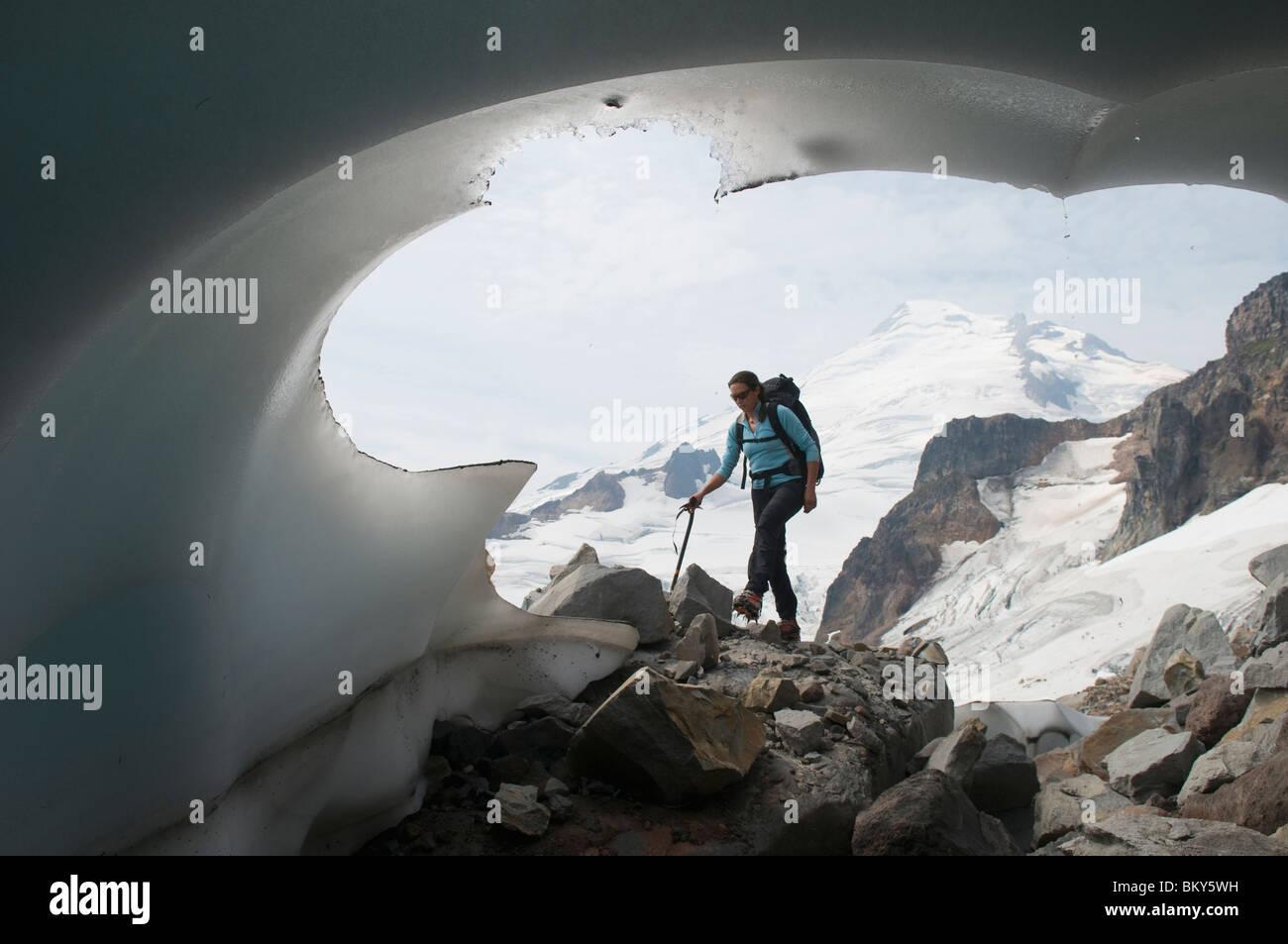 Una donna di alpinismo passando un capolinea glaciale, il Monte Baker deserto, Bellingham, Washington. Immagini Stock