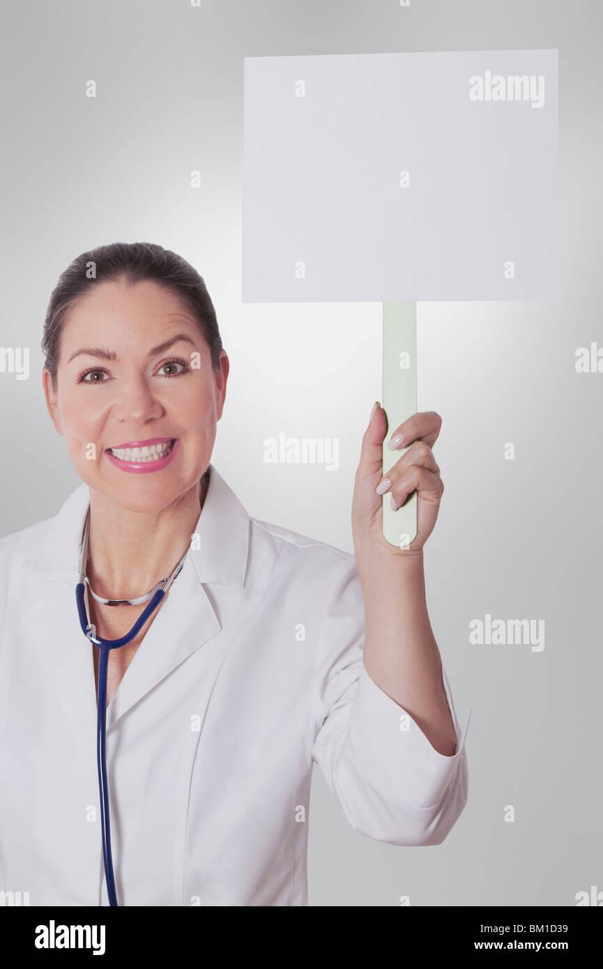 Medico donna tenendo un cartello bianco Immagini Stock