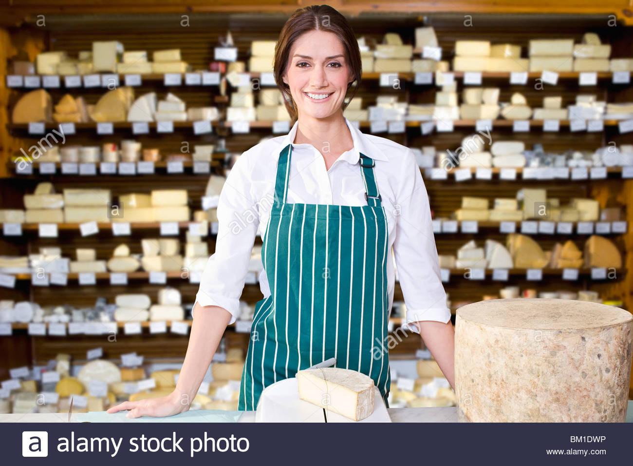 Proprietario del negozio in piedi con la grande varietà di formaggi Immagini Stock