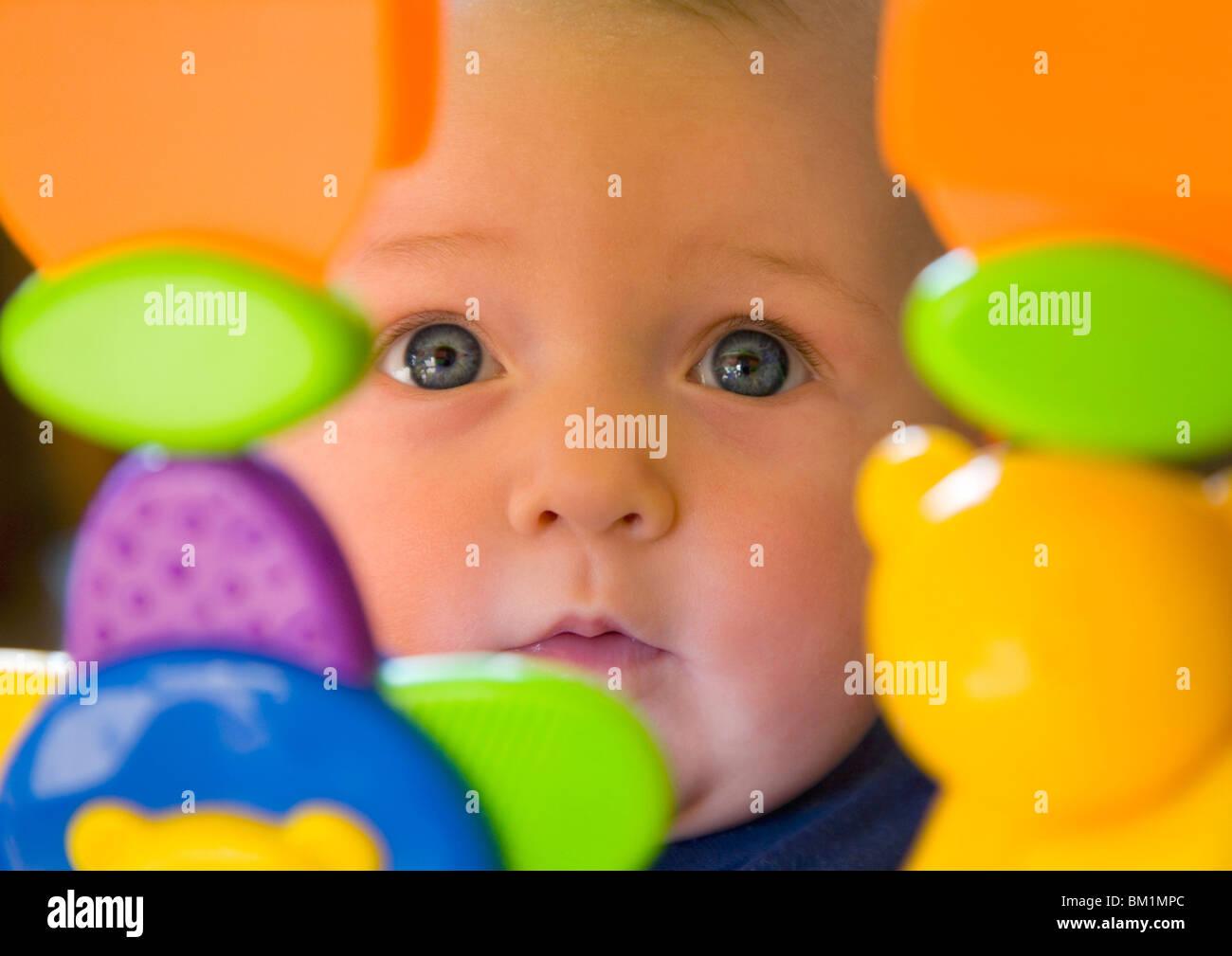 Bambina di 6 mesi per bimbi con gli occhi blu guardando attraverso dei giocattoli di plastica Immagini Stock