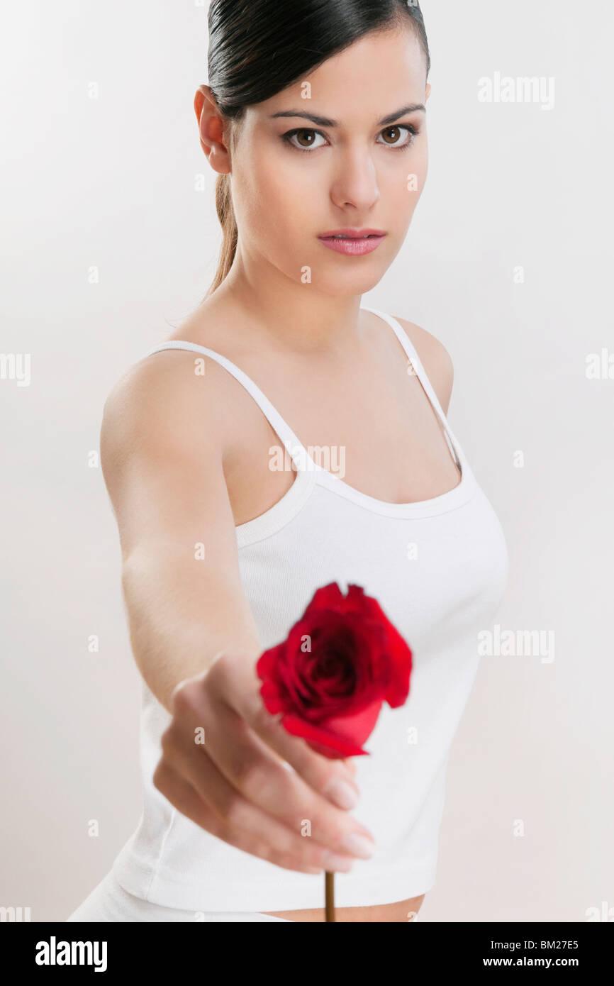 Ritratto di una donna che mantiene una rosa Immagini Stock