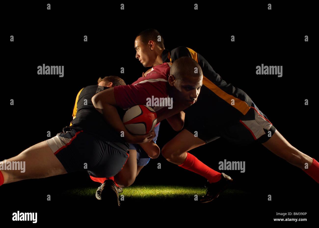 Giocatore di Rugby affrontato da due avversari Immagini Stock