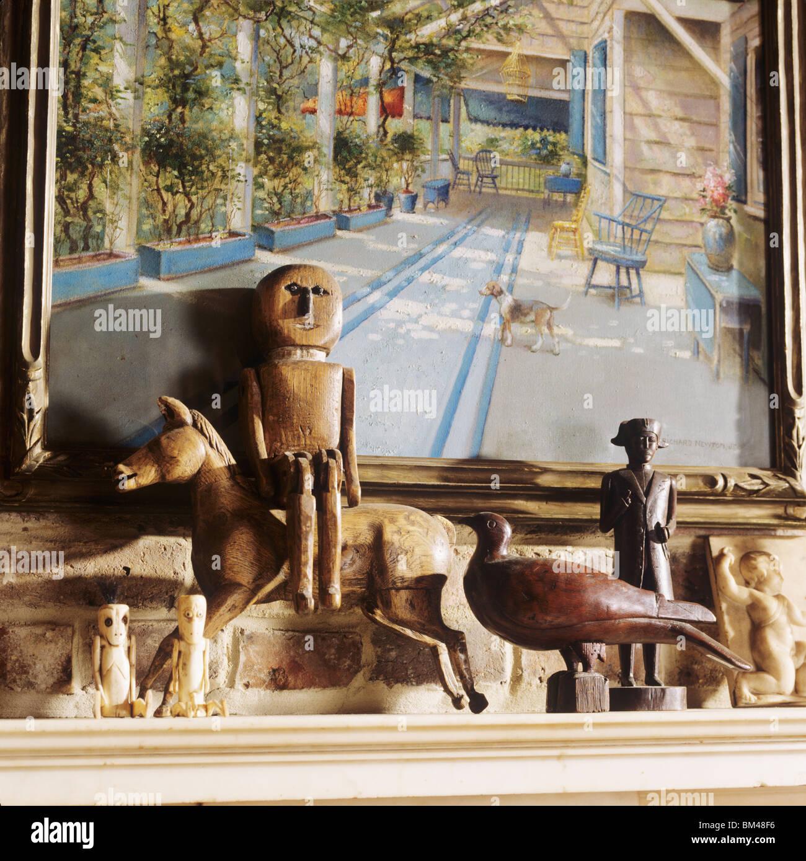 Una collezione di figurine di legno su un mantelpiece Immagini Stock