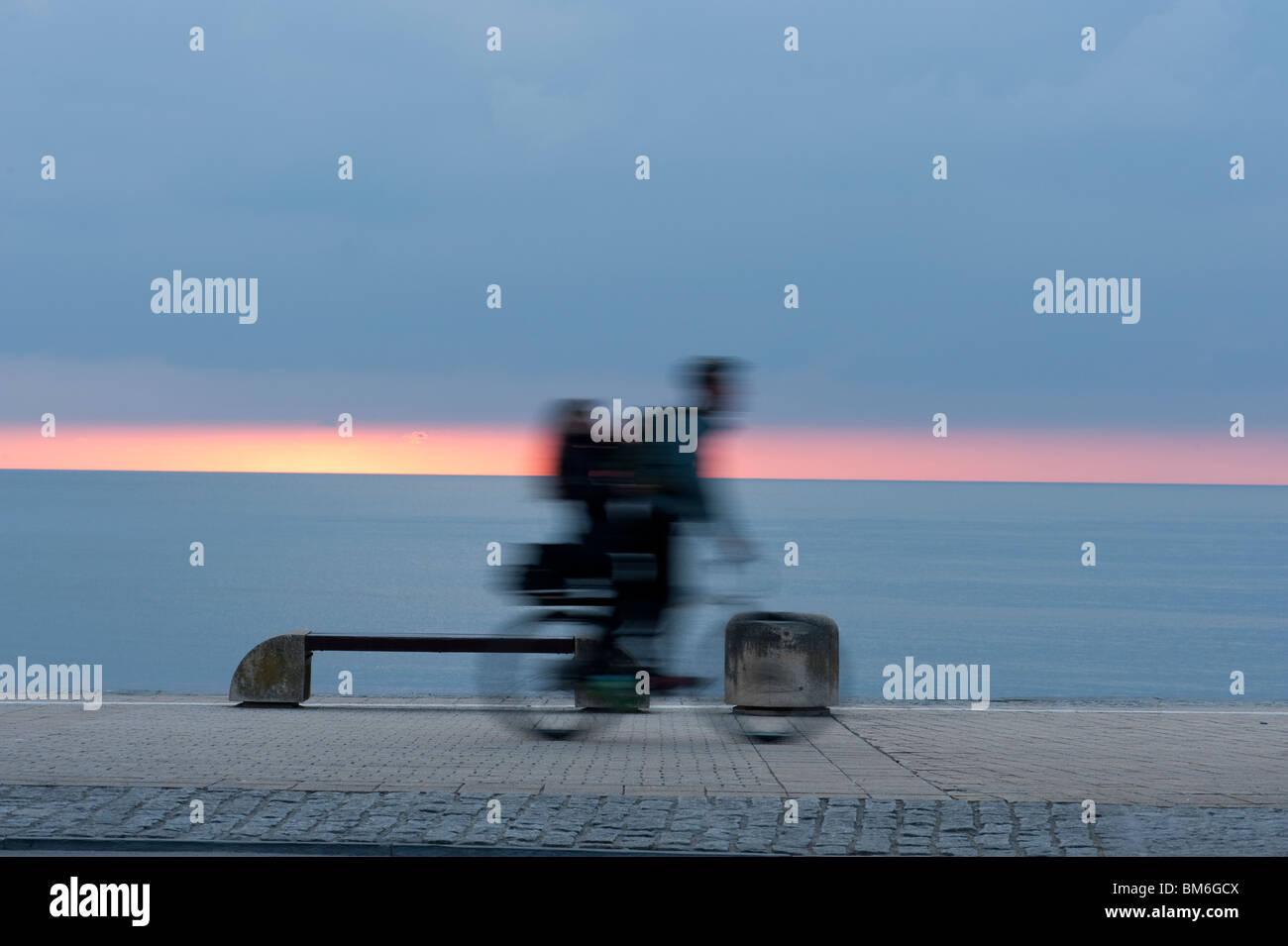 Sfocatura di movimento del ciclista in ther crepuscolo serale, Aberystwyth promenade, località balneare, west Immagini Stock