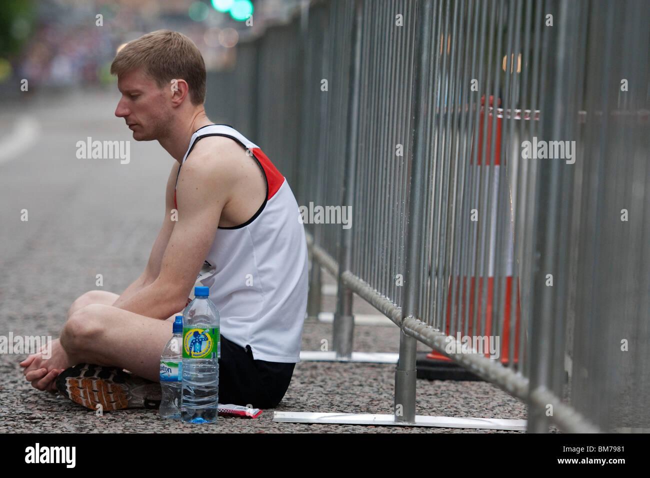 Un concorrente si siede da solo prima di iniziare la Scottish mezza maratona, parte della Maratona di Edimburgo Immagini Stock