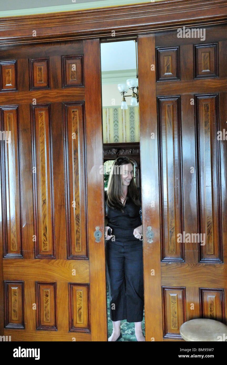 Jen Eastwood chiude il legno lucidato le porte di separazione per il soggiorno e la cucina della storica casa di Immagini Stock