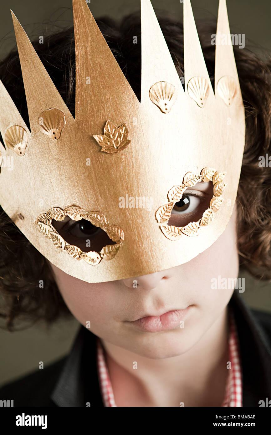 Ragazzo che indossa corona d'oro maschera Immagini Stock